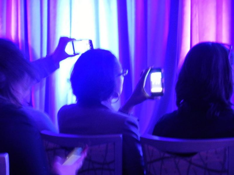 Conference participants are filming a presentation on their smartphones.